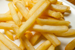 Tasty golden french fries on a plate. Stock Photos