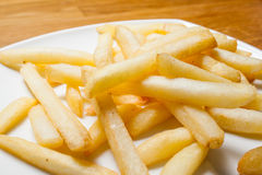 Tasty golden french fries on a plate. Royalty Free Stock Image