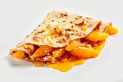 Tasty golden fried crepe with fresh mandarin. Orange filling drizzled wit a fruity syrup and topped with zest on a white background suitable for advertising stock image