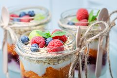Tasty granola with fresh fruits and yoghurt in jar. On white background royalty free stock image