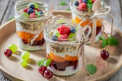 Tasty granola in jar with yoghurt and berry fruits. On wooden tray stock photography