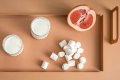 Grapefruit, marshmallows and glasses with milk Royalty Free Stock Photography