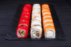 Tasty great colorful set of fresh japanese sushi maki philadelph. Ia and california rolls served on black slate, close up. Food art, traditional seafood Stock Image