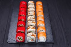Tasty great colorful set of fresh japanese sushi maki philadelph. Ia and california rolls served on black slate. Food art, traditional seafood, restaurant menu Royalty Free Stock Photo