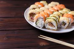 Tasty great colorful set of fresh japanese sushi maki rolls serv. Ed on round plate,with chopsticks, close up. Food art, traditional seafood, restaurant menu Stock Photo