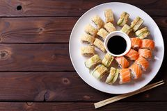 Tasty great colorful set of japanese sushi maki rolls with salmo. N, tuna and avocado served on round plate, with soy sauce and chopsticks, flat lay. Food art Stock Photography