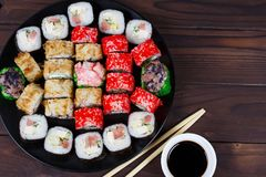 Tasty great set of japanese sushi maki rolls served on round pla. Te, with soy sauce and chopsticks, flat lay. Food art, traditional seafood, restaurant menu Royalty Free Stock Photography