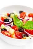 Tasty greek salad with bright vegetables, garnished with basil. Stock Image