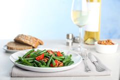 Tasty green beans with walnuts and tomatoes served. For dinner on table stock images