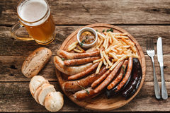 Tasty grill sausages. Oktoberfest meal, top view. Traditional German food. Mug with beer and delicious grilled sausages and french fries served with bread buns Royalty Free Stock Photos