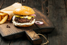 Tasty grilled beef burger with potatoes on a dark board Stock Images