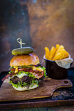 Tasty grilled beef burger with spinach lettuce and blue cheese s Royalty Free Stock Photo