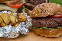 Tasty grilled burger, fried potato and glass of beer. Royalty Free Stock Image