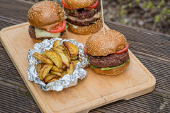 Tasty grilled burger, fried potato and glass of beer. Royalty Free Stock Photo