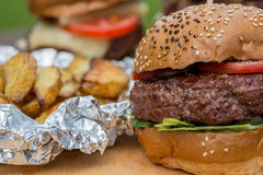 Tasty grilled burger, fried potato and glass of beer. Royalty Free Stock Images