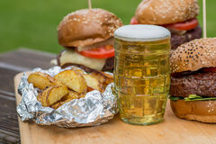 Tasty grilled burger, fried potato and glass of beer. Stock Photo