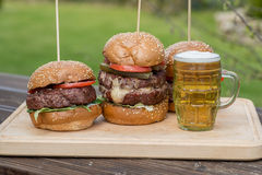 Tasty grilled burger and glass of cold beer. Stock Images