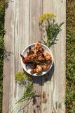 Tasty grilled chicken drumsticks and wings on a white plate, top view. Tasty grilled chicken drumsticks and wings on a white plate. Plate is on the old painted Royalty Free Stock Photo
