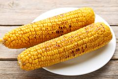 Grilled corns. Tasty grilled corns on grey wooden table Royalty Free Stock Photos