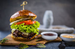 Tasty grilled glazed beef burger with lettuce and cheese served Stock Images
