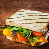 Tasty grilled herb and cheese sandwich. On two slices of bread with rocket and spinach, pepper and tomato on a rustic wooden table for a healthy lunchtime snack stock photos