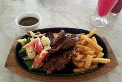 Tasty Grilled lamb chop with variety of vegetables and french fries served on hot plate Royalty Free Stock Photography