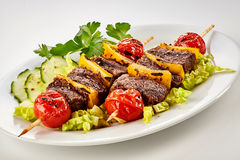 Tasty grilled marinated beef shish kebabs. With colorful bell pepper and tomato on wooden sticks served on a bed of fresh salad with cucumber and coriander Royalty Free Stock Photos