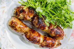 Tasty grilled meat sausages. On a dish Royalty Free Stock Image