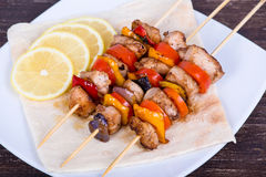 Tasty grilled meat and vegetables on skewer Stock Photos