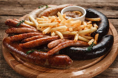 Tasty grilled sausages and french fries close up. Traditional Oktoberfest menu. Various sausages served with sauce and french fries on wooden table, close up Stock Images