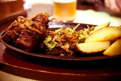 Tasty grilled steak meat with fries potatoes Stock Photography