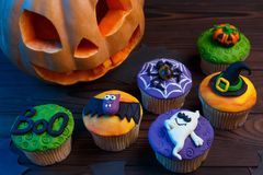 Tasty Halloween cupcakes set with colorful decorations made of c stock photo