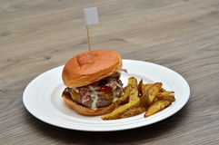 Tasty hamburger with flag and potato on white plate Stock Photography