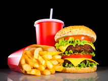 Tasty hamburger and french fries on a dark Royalty Free Stock Image