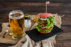 Tasty hamburger with meat and vegetables against a dark background royalty free stock photos