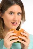Tasty hamburger - woman enjoying fast food. Female eating fresh tasty hamburger with greenery Royalty Free Stock Images