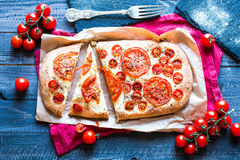 Tasty Hand Made Tomatoes Pizza Bread. With italian style recipe over a wooden table with a Dramatic light royalty free stock photo