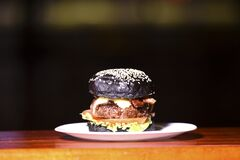 Tasty handmade hamburger sandwich with black bread onion tomato lettuce and bread served on top of a stone on black background