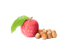 Tasty hazelnuts and fresh apple on a white. Royalty Free Stock Photo