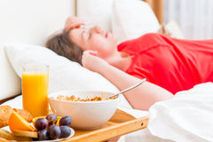 Tasty and healthy breakfast in the focus. On the background of the sleeping woman Royalty Free Stock Photos