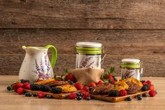 Tasty and healthy breakfast, forest fruits, chocolate scones and milk recipients. royalty free stock photos