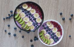 Healthy oatmeal with fruits and yoghurt. Tasty and healthy breakfast. Fresh oatmeal with blueberry yoghurt, bananas, kiwi and currants. Closeup photo. Top view royalty free stock image