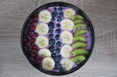Healthy oatmeal with fruits and yoghurt. Tasty and healthy breakfast. Fresh oatmeal with blueberry yoghurt, bananas, kiwi and currants. Closeup top view photo royalty free stock photo