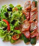 Tasty And Healthy Dinner. Vegetable marrow wrapped in bacon, and salad made of tomatoes, lettuce, onion and black olives stock photo