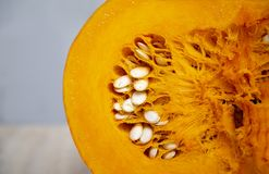 Tasty, healthy and fleshy vegetable-juicy, bright orange pumpkin oval. Tasty and healthy and fleshy vegetable - juicy, bright orange pumpkin in a cut with seeds stock image