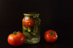 Tasty and healthy food for your health. Cucumbers and tomatoes in a glass jar. some are fresh. dark background Royalty Free Stock Photo
