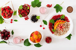 Tasty and healthy oatmeal porridge with berry, flax seeds and smoothies Stock Photography