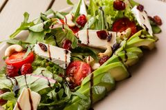 Tasty and healthy salad with arugula, brie, cheese, avocado, cherry tomatoes, dry cranberry and cashews. Top view. The royalty free stock photo