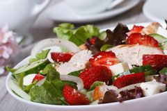 Tasty and healthy salad of strawberries, chicken, vegetables. Tasty and healthy salad of strawberries, feta cheese, vegetables and chicken breast macro Royalty Free Stock Image