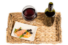 Tasty healthy salmon meal. Overhead view of a tasty healthy meal of salmon steak served on a rustic woven tray with a glass and bottle of red wine Stock Photography